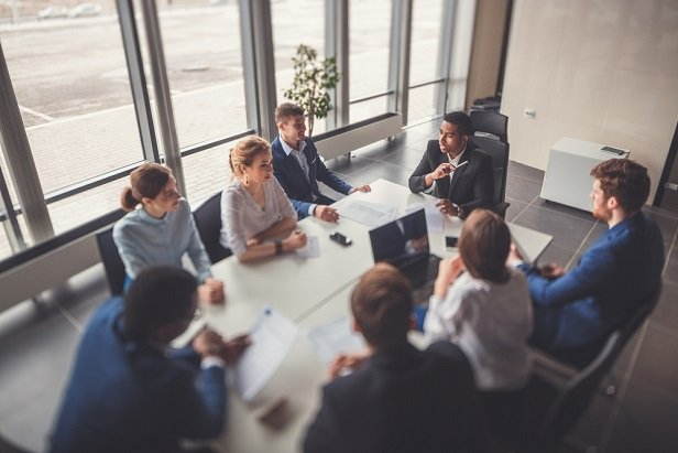 men and women sitting around conference table in meeting