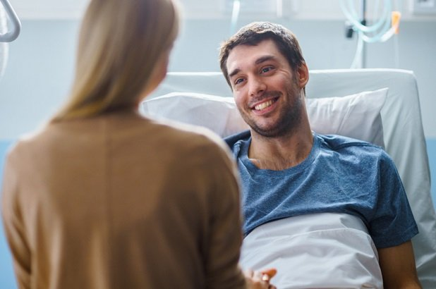 smiling man in hospital bed talking to visitor