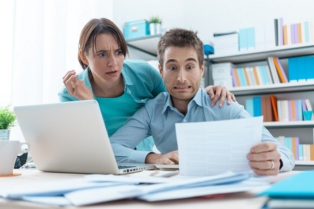 man and woman at laptop looking shocked