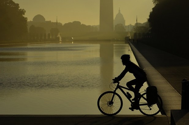 cyclist backlit with Washington Monument in background