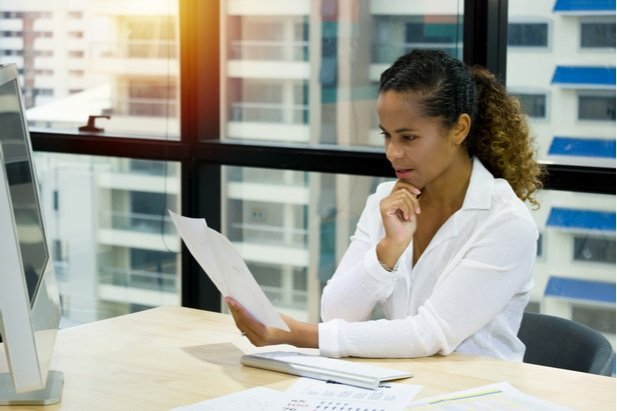 young businesswoman at desk reading and thinking
