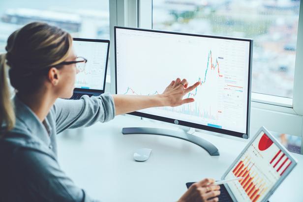woman pointing at charts on monitor screen