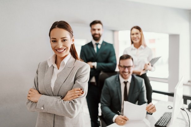 business woman and employees standing with arms folded but smiling