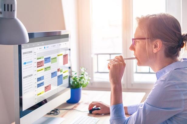 woman at desk looking at her desktop computer