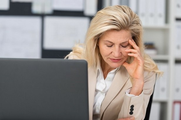 older middle age woman at computer looking stressed