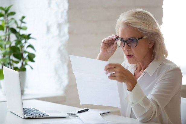 older woman at computer looking shocked