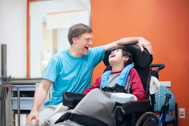 child in wheelchair laughing beside seated man