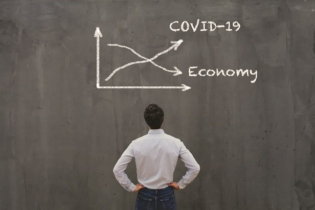man looking at chalkboard with down arrow labeled economy and up arrow labeled COVID-19