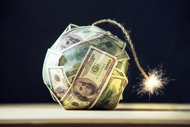 dollar bills formed into a model of a time bomb with fuse