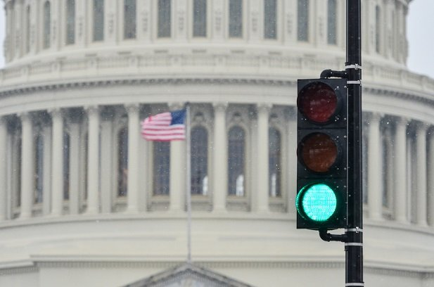 closeup of nation's capitol building with flag and green light