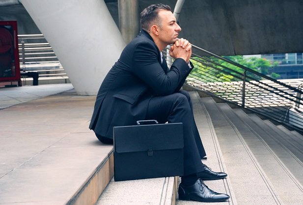 businessman sitting on stairs looking pensive and sad