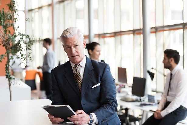 white haired business man looking at tablet in office
