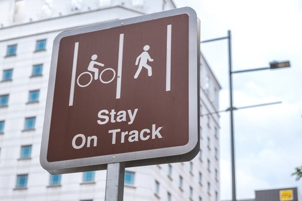 street sign saying stay on track with pedestrian and cyclist symbols