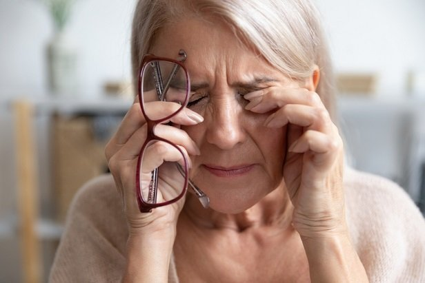 stressed older woman rubbing eyes.