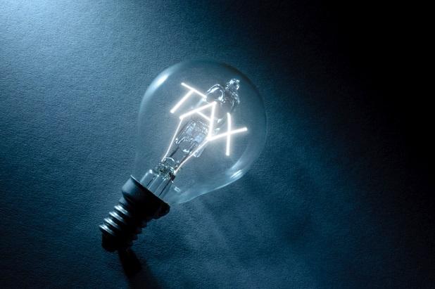 lightbulb with lit word Tax in dark background