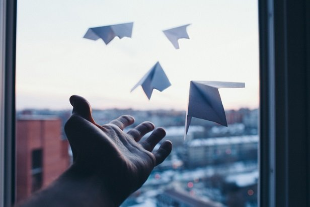 man's hand throwing paper airplanes out of window high above city