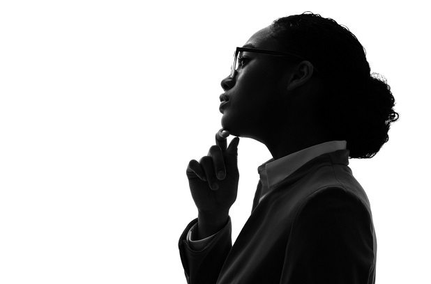 business woman in silhouette looking pensive