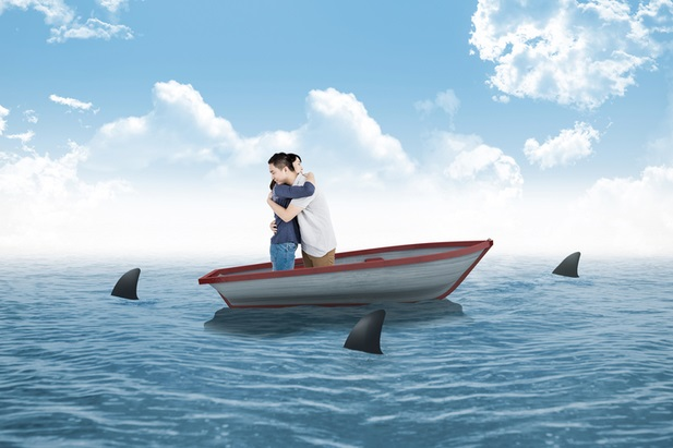 man and woman in boat surrounded by sharks