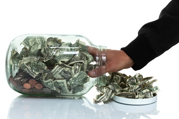 Man pulling cash out of a jar.