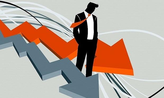 Businessman standing between two downward-trending arrows
