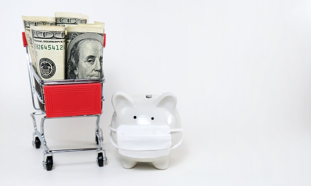Piggy bank wearing mask next to shopping car with dollars