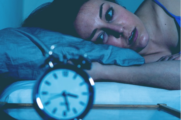 CEO female awake and staring at clock that reads 3 30 in the morning