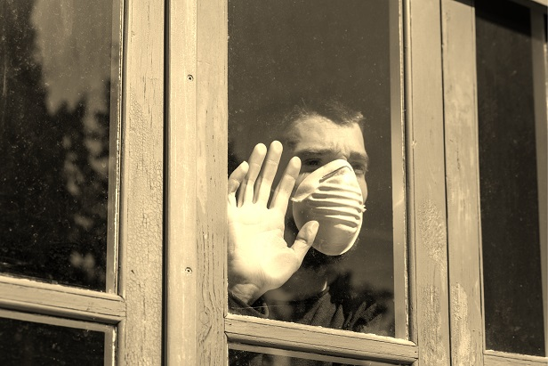 man wearing face mask standing at window