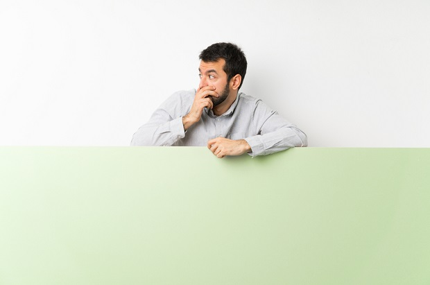 man leaning over partial wall looking stressed and holding hand to mouth