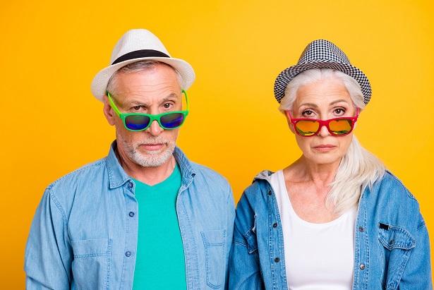 Senior couple wearing hats and eyeglasses.