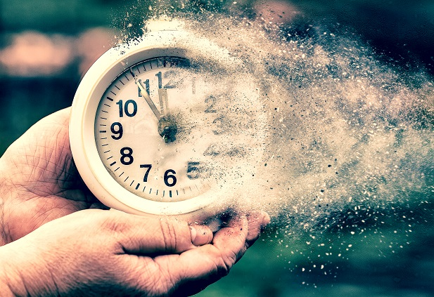 woman's hands holding a clock that is turning to dust