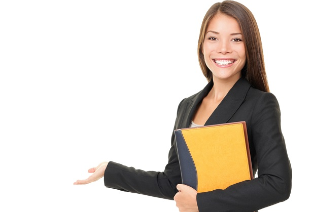 woman in business suit holding folder with hand to side as if showing someting