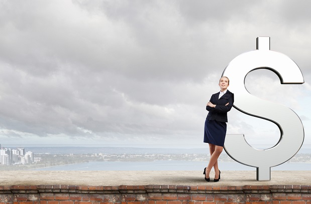 businesswoman leaning against giant dollar sign