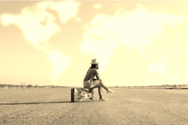 woman sitting on empty land on her suitcase waiting
