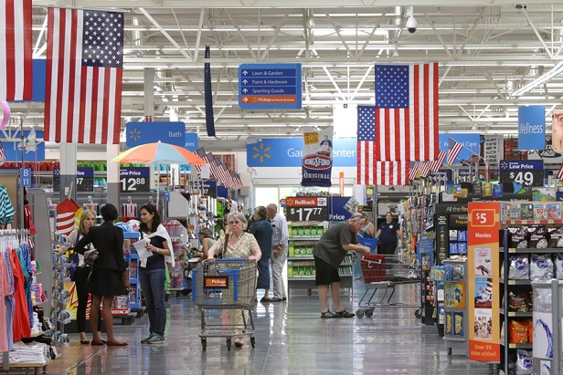 inside of a Walmart store showing shoppers, carts, flags