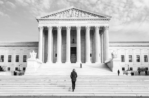 black and white image of front of Supreme Court with steps and figure standing in front