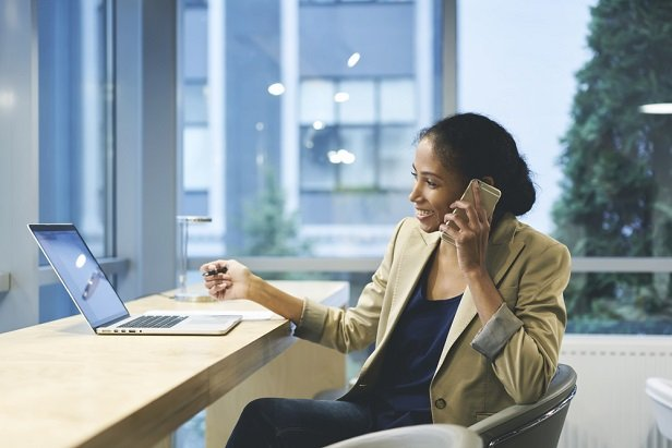 business woman in front of laptop at window talking on phone