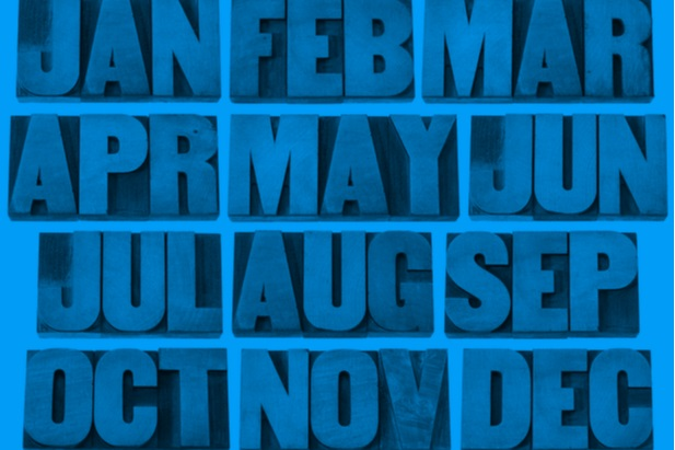the months of the year abbreviations on wood blocks in a grid that is blue