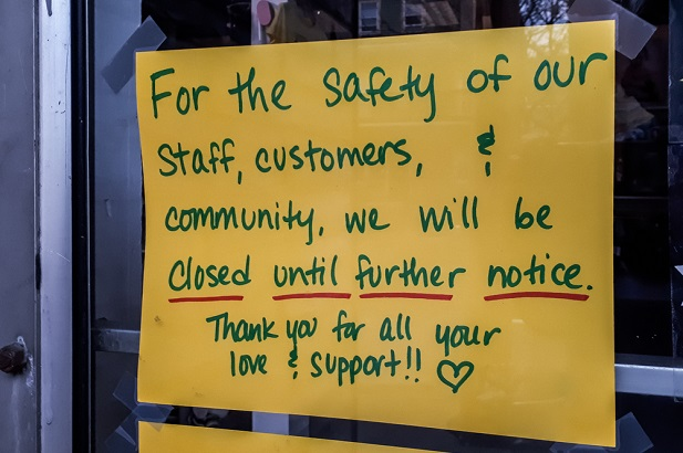 sign in business window saying it is closed for safety of customers