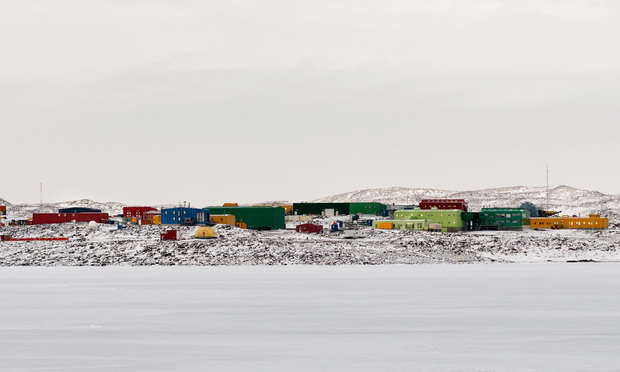 Davis Station in Antarctica showing a small line of colorful tiny buildings surronded by white above and below, snow and ice.