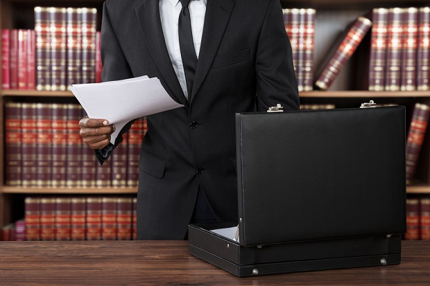 man in business suit in front of legal volumes with papers in hand
