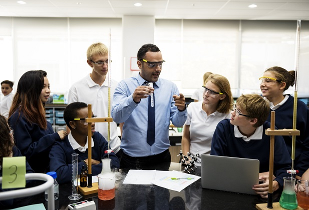 Male teacher working with students in classroom.