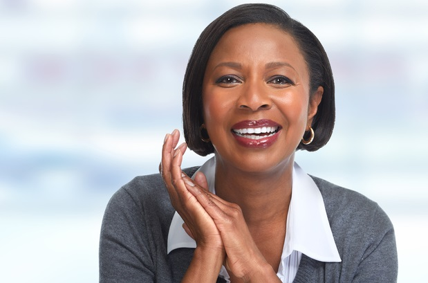 business woman looking at camera and smiling, with hands clasped