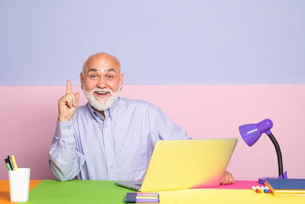 older bearded man in front of pastel background and laptop smiling