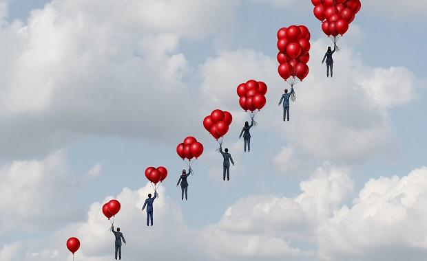 Businessmen being carried away by balloons