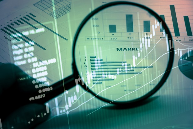 magnifying glass and collage of stock charts