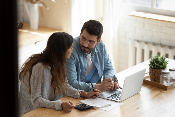 man and woman at computer discussing finances
