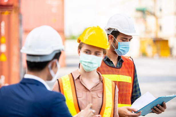 engineer and hard hat workers wearing face masks at job site