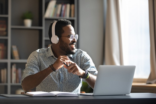 man with headphones sitting at work computer smiling