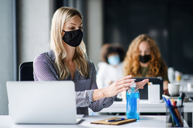female office workers wearing mask while working at socially distanced workstations