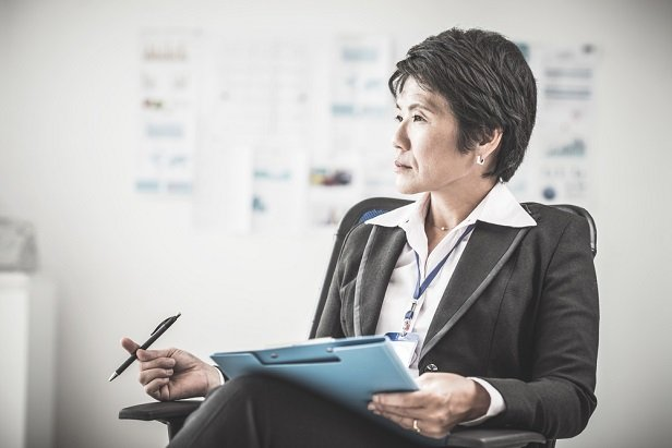 female executive in chair with pencil and notes looking in distance and thinking